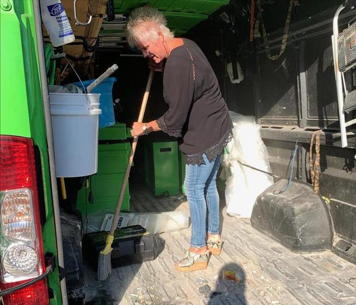 Owner sweeping out dirty van